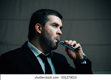 Young businessman smoking electronic cigarette. Close-up portrait