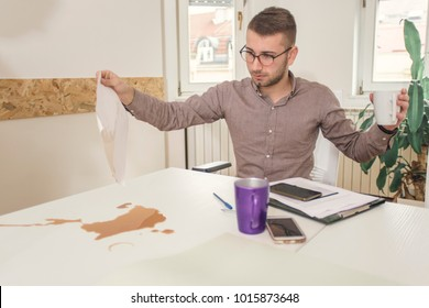 Young businessman spill coffee on a working desk and paperwork.  Business concept.