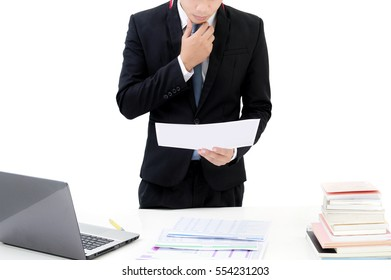 Young businessman standing behind office desk and reading documents