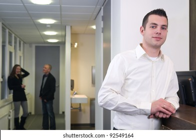 Young businessman standing at a desk with colleagues in the background