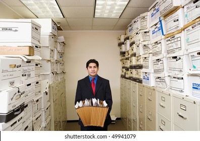A young businessman is standing in a file room holding files. Cabinets and storage boxes line the sides. Horizontal shot.