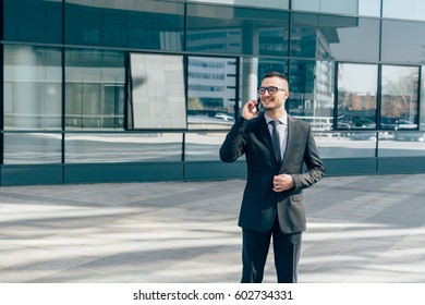 Young businessman standing in front of office by day and talking on the phone