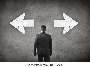 Young businessman standing in front of two arrows showing two different directions