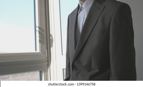 Young businessman standing in front of windows looking into distance on the city