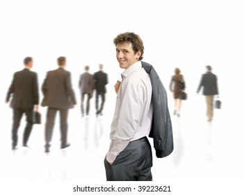 Young businessman standing his suit draped over his shoulder, looking back. Businesspeople moving in the background, isolated on white.