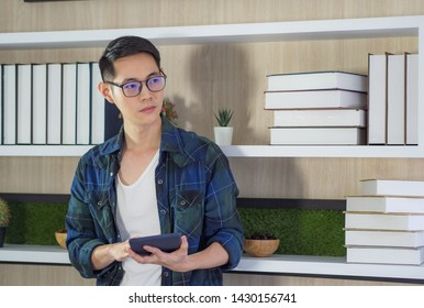 Young businessman standing holding the tablet expressing anxiety and looking up for ideas and using ideas find ideas for work in his office. Asian young man using thinking positive for problem
