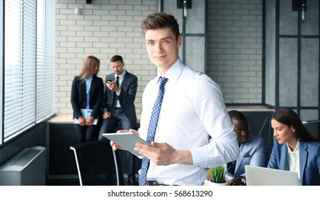 Young businessman standing in office with his collegue on the background