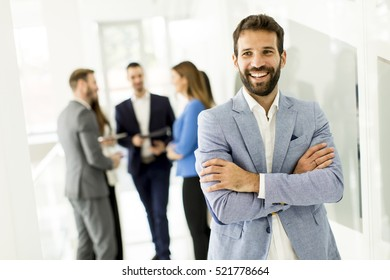 Young businessman standing in the office and other young business people talking at background
