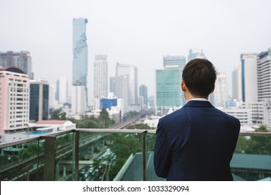 Young businessman standing on balcony looking at city view in Bangkok city, Thailand