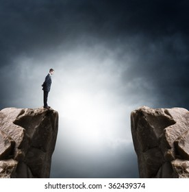 Young businessman standing on edge of rock mountain and looking