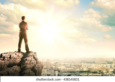Young businessman standing on edge of rock mountain and looking at city