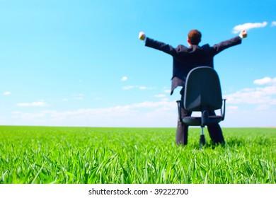 Young businessman standing on green field near chair. Focus on grass