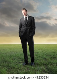 Young businessman standing on a green meadow