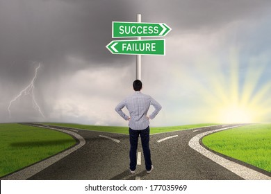 Young businessman is standing on the road with a sign of success or failure