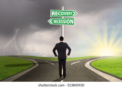 Young businessman standing on the road and looking at a signpost with two choices of recession or recovery finance