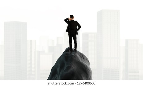 Young businessman standing on rock mountain and looking at the city landscape