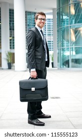 Young businessman standing out of a modern building