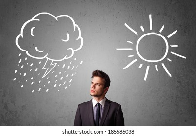 Young businessman standing and wondering between the sun and rain drawings
