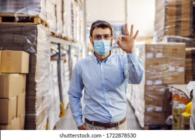 Young businessman with sterile protective mask on standing in warehouse and showing okay sign. Protection from corona virus/ covid-19.
