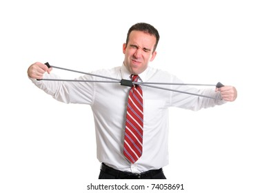 A young businessman straining to stretch a resistance band, isolated against a white background.
