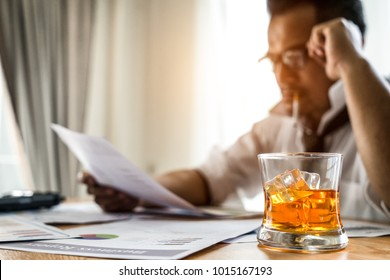Young businessman stressful headache with work his office while sitting at desk and Booze and smoking to relax.
