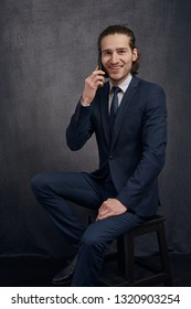 Young businessman in a stylish suit seated on a stool chatting on a mobile phone smiling at the camera with a happy friendly expression against a dark grey studio background
