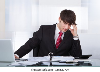 Young businessman suffering from headache while calculating finance at desk in office