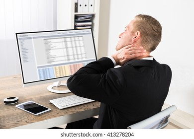 Young Businessman Suffering From Neck Ache While Using Computer At Office