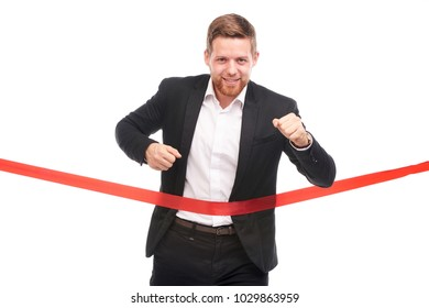 Young businessman in suit crossing finish red ribbon first
