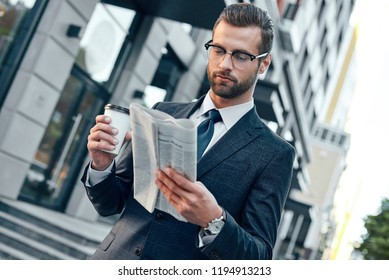 Young businessman in suit and glasses holding a paper cup and reading business newspaper in his hands