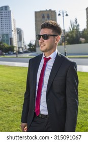 Young businessman  in a suit and glasses and red tie.