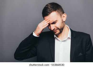 Young businessman in suit head pain  isolated