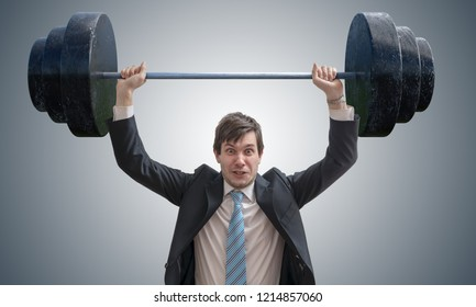 Young businessman in suit is lifting heavy weights.