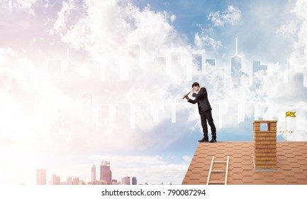 Young businessman in suit on roof edge. Mixed media
