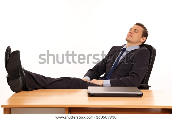 Young businessman at suit relaxes in work and sleeps