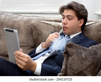 Young businessman in a suit relaxing on a comfortable sofa with an e-cigarette puffing away as he reads his tablet computer