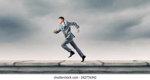 Young businessman in suit running on road