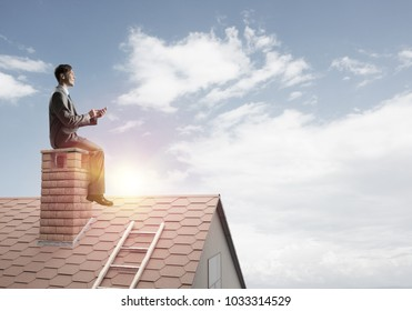 Young businessman in suit sitting on house with red book in hands
