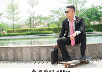 Young businessman in suit sitting outdoors with a briefcase and a skateboard