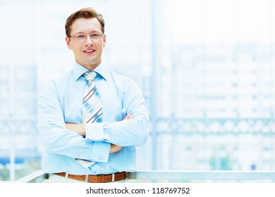 Young businessman in suit working in bright office, standing