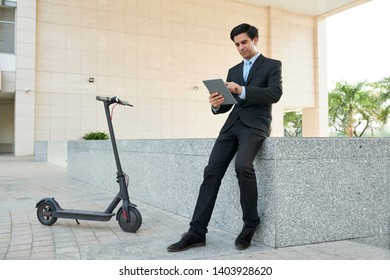 Young businessman in suit working online on digital tablet while sitting in the city with electric scooter