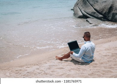 young businessman in sunglasses blue shirt and shorts working with laptop on the beach