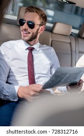 young businessman in sunglasses with newspaper on backseat of car