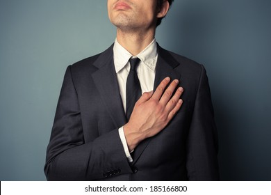 Young businessman is swearing allegiance with his hand on his chest
