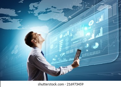 Young businessman with tablet in hands against digital background