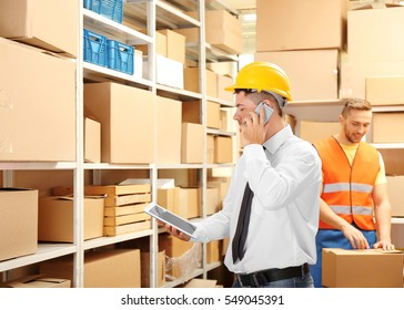 Young businessman with tablet at warehouse