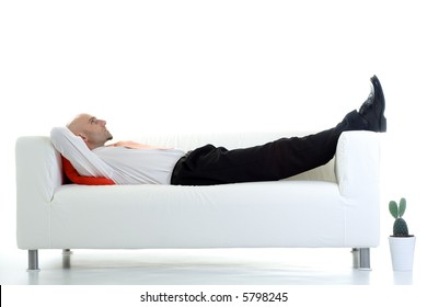 A young businessman takes a short break and lies down on the couch.