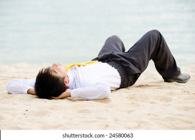young businessman taking a break at the beach