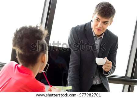 Young businessman taking a coffee break, listening to his colleague in the office
