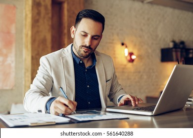 Young businessman taking note beside laptop on table in cafe